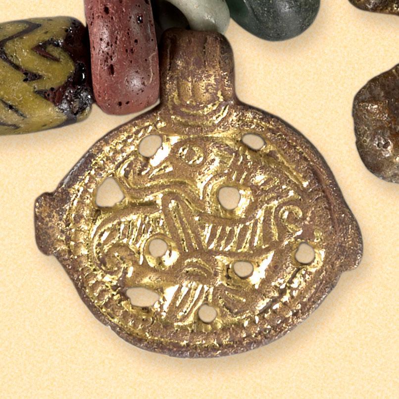 Brakteat i bronse. Utført i Jellingstil, og forestiller et sammenkrølet dyr. Smykket ligger lagret hos Kulturhistorisk Museum, UiO i Oslo. Museumsnummer c5454.