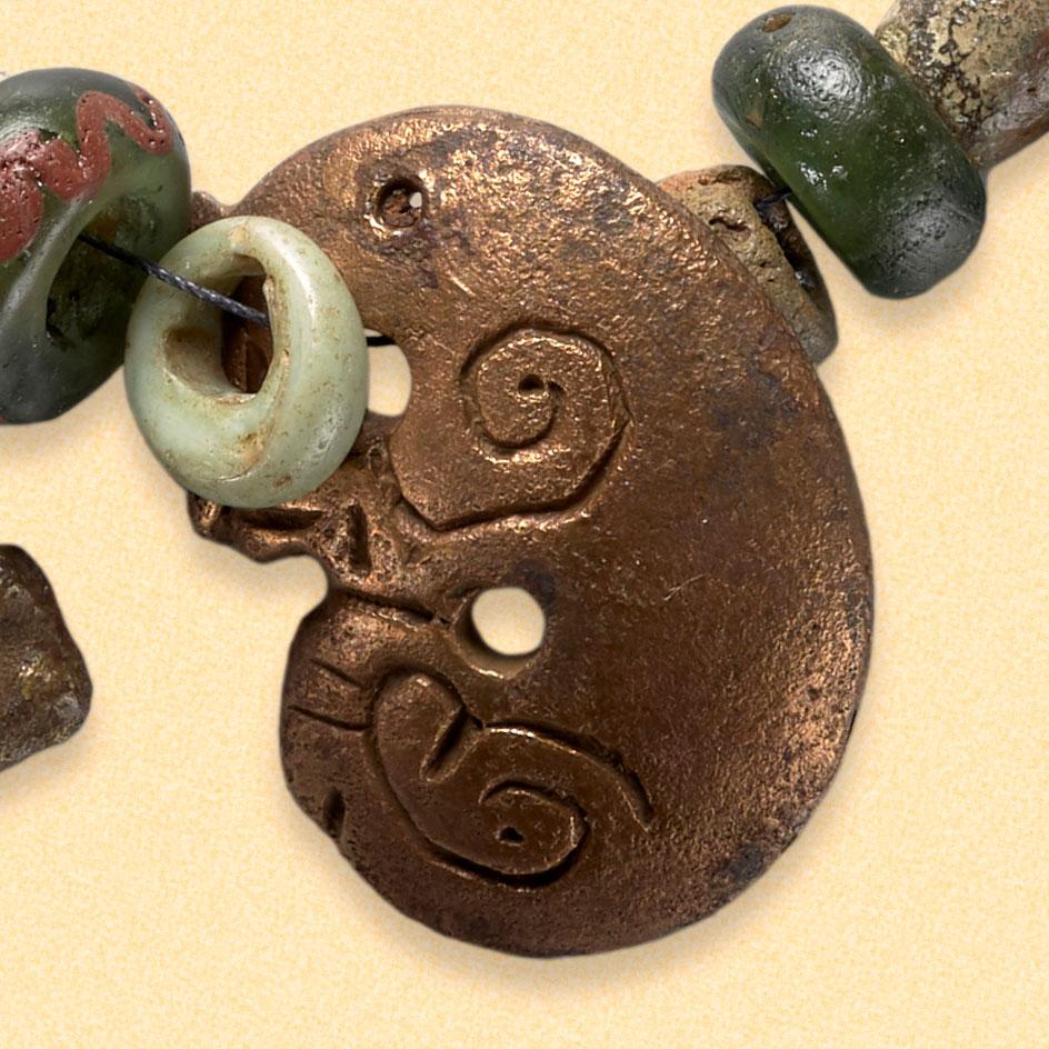 Bronseanheng på smykkefunn. Forestiller er sammenkrølet dyr. Smykket ligger lagret hos Kulturhistorisk Museum, UiO i Oslo. Museumsnummer c5455.